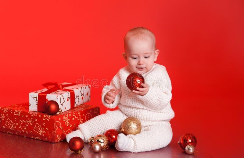 Bébé garçon mignon s'asseyant sur le plancher avec le décor de Noël photos libres de droits