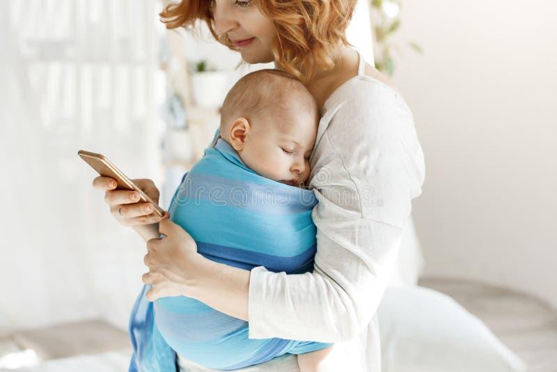 Bébé garçon minuscule ayant des rêves agréables dans la bride de bébé tandis que la mère se repose et regardant par les réseaux s photo libre de droits