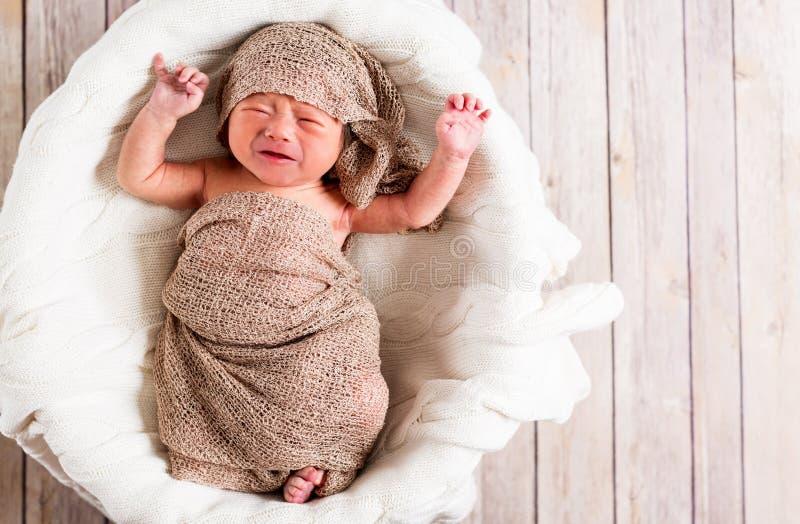 Bébé garçon pleurant dans un panier images libres de droits