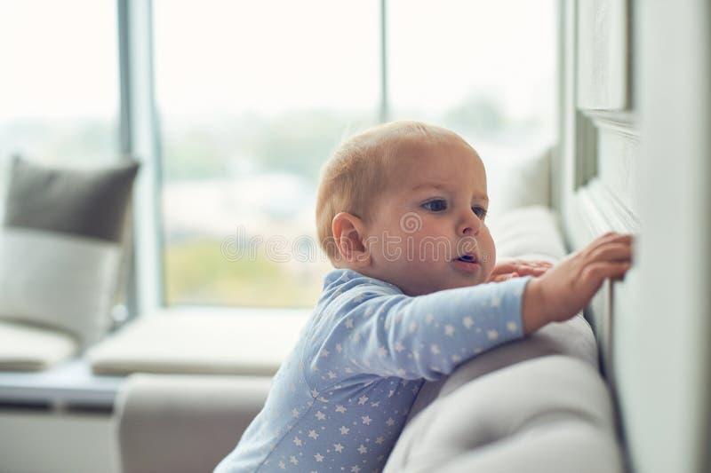 Bébé garçon rampant et s'élevant sur le sofa à la maison photos libres de droits