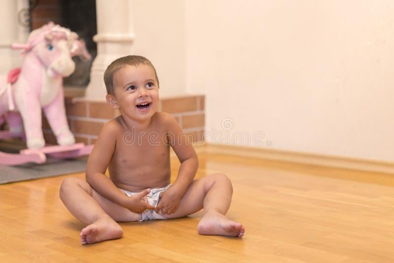 Bébé garçon riant dans la salle de jeux Bébé garçon mignon riant et montrant des dents de lait avec des jouets sur un fond troubl photo stock