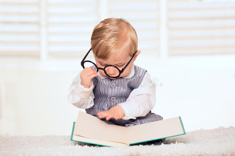 Bébé garçon ringard lisant un livre photographie stock libre de droits