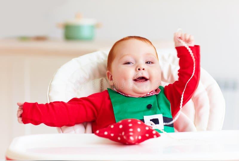 Bébé garçon roux infantile mignon dans le costume d'elfe jouant avec l'étoile rouge dans le highchair image libre de droits