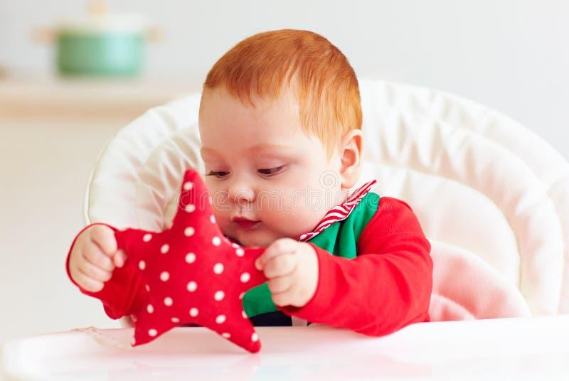 Bébé garçon roux infantile mignon dans le costume d'elfe jouant avec l'étoile rouge dans le highchair photo stock
