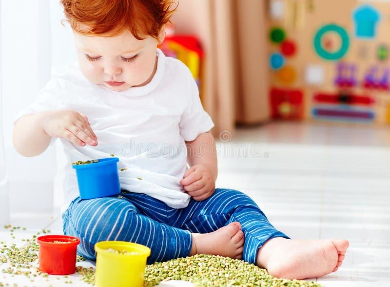 Bébé garçon roux mignon développant ses qualifications fines de motilité en jouant avec les pois à la maison photo libre de droits