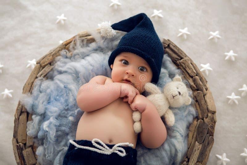 Bébé garçon se situant dans un panier avec le chapeau-tricotage de fourrure photographie stock
