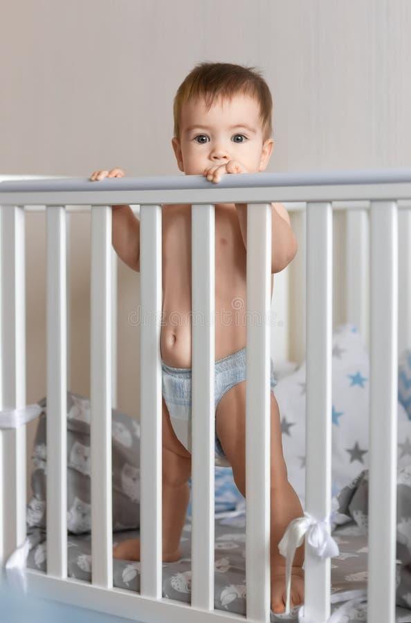 Bébé garçon se tenant dans la huche photos stock