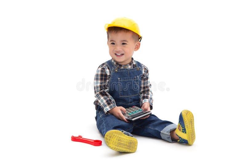 Bébé garçon thaïlandais asiatique portant un costume d'ingénieur avec le casque antichoc et jugeant la calculatrice d'isolement s image stock