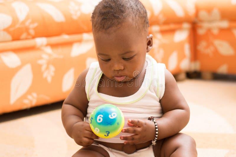Bébé heureux jouant avec des boules dans la maison photographie stock