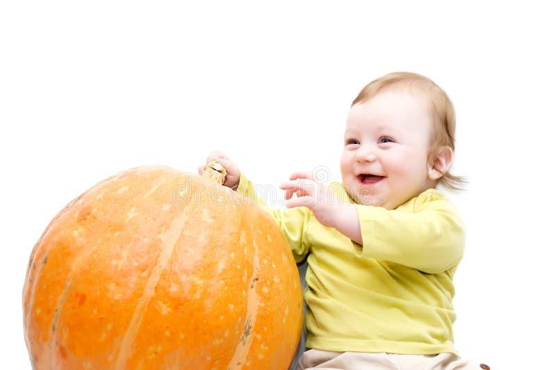Bébé heureux jouant avec le potiron image libre de droits