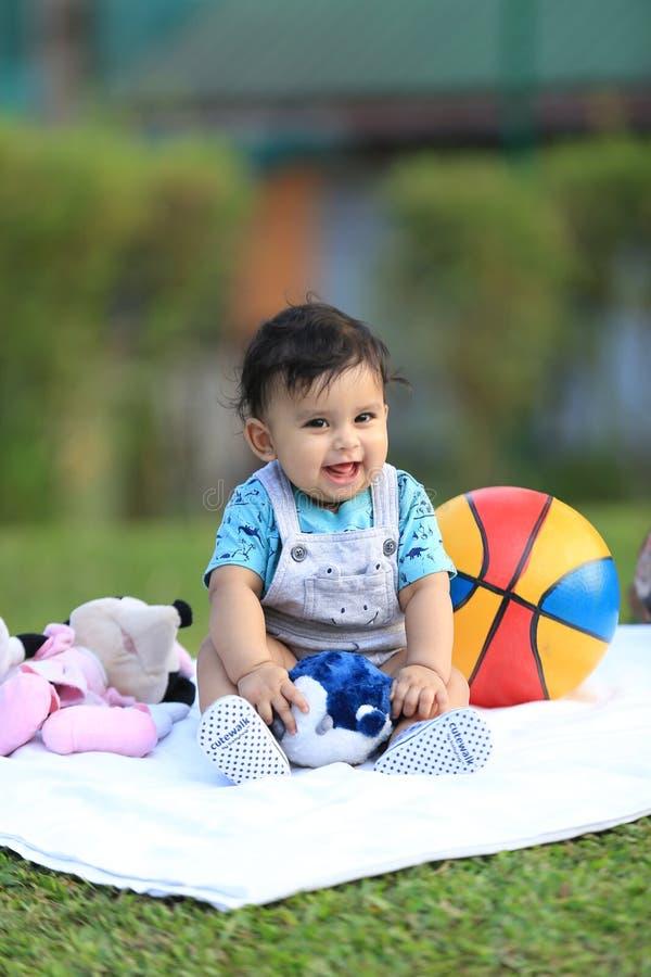 Bébé heureux jouant dehors avec la boule colorée photos stock
