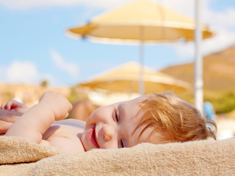 Bébé heureux prenant un bain de soleil sur le lit pliant de plage images stock