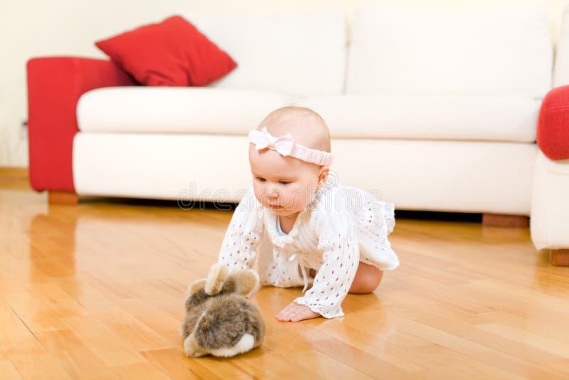 Bébé heureux rampant au jouet de lapin photos stock