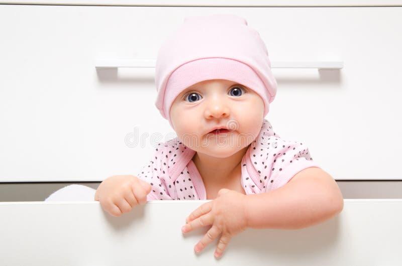 Bébé heureux s'asseyant dans un coffre de tiroir image libre de droits