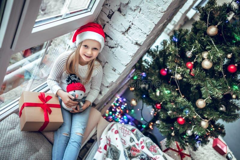 Bébé heureux s'asseyant sur la fenêtre avec le cadeau de Noël images libres de droits