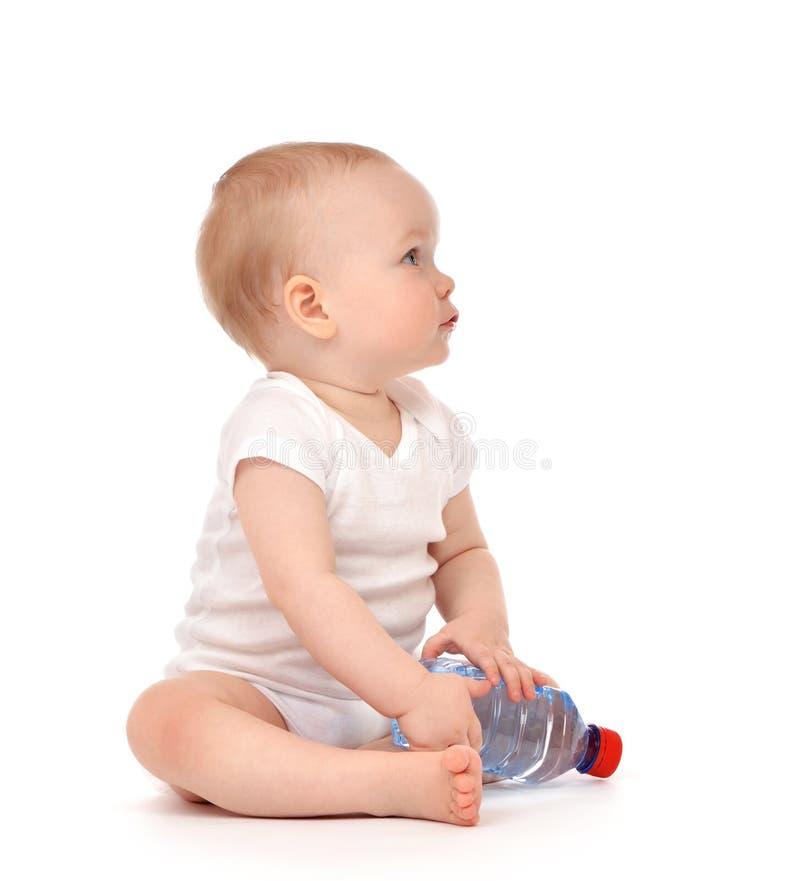 Bébé infantile d'enfant s'asseyant avec la bouteille d'eau potable dans la couche-culotte photographie stock libre de droits