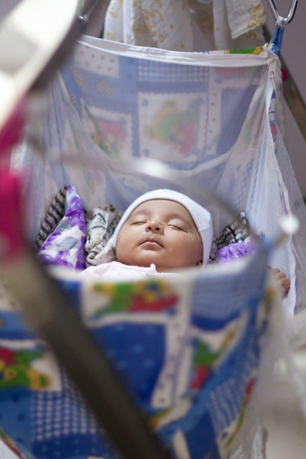 Bébé infantile indien dormant dans l'oscillation bleue photographie stock libre de droits