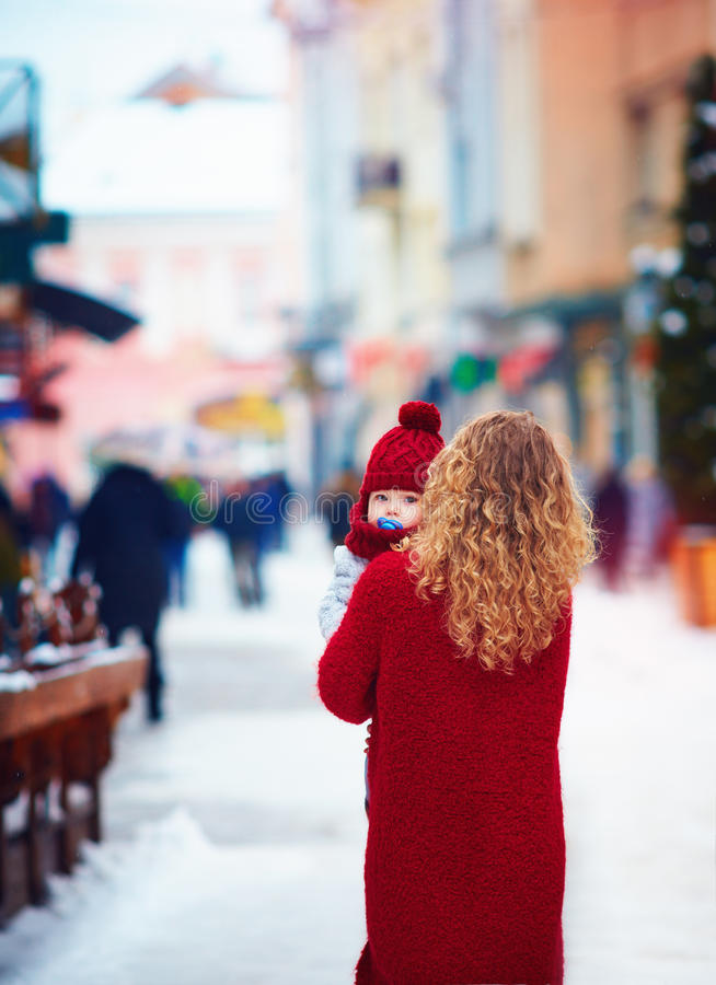 Bébé infantile mignon sur la main du ` s de mère sur la rue serrée de ville en hiver photographie stock libre de droits