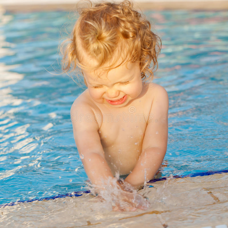 Bébé jouant avec de l'eau dans la piscine image stock