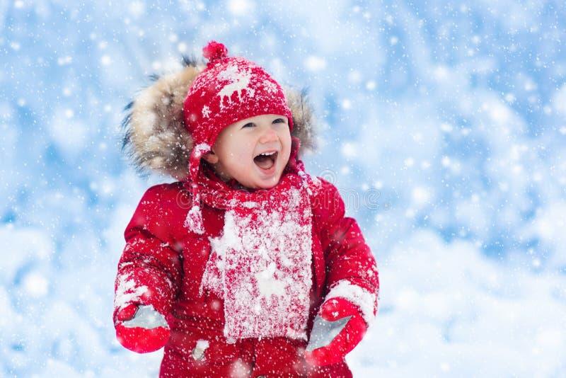 Bébé jouant avec la neige en hiver images libres de droits