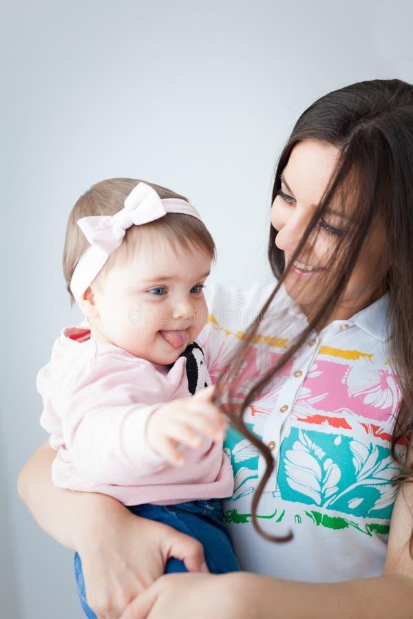 Bébé jouant avec les cheveux de sa maman photo stock