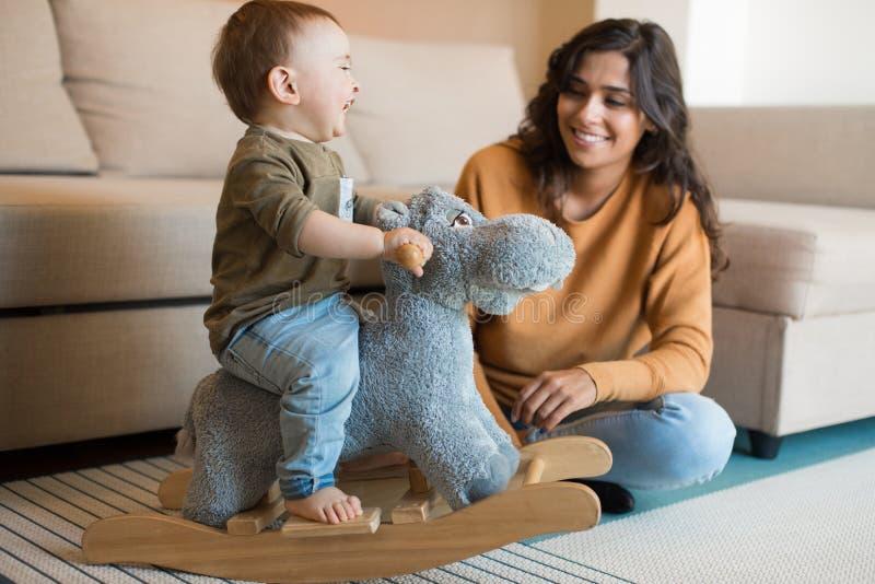 Bébé jouant avec un cheval de basculage photo stock