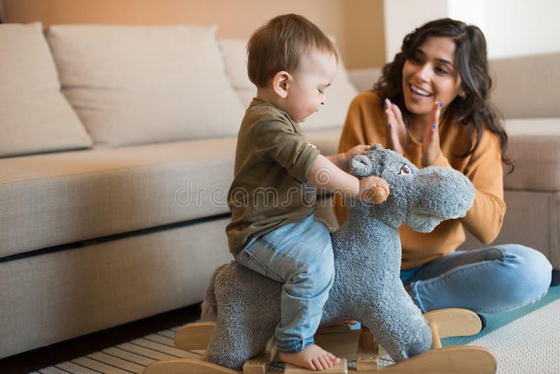 Bébé jouant avec un cheval de basculage photographie stock libre de droits