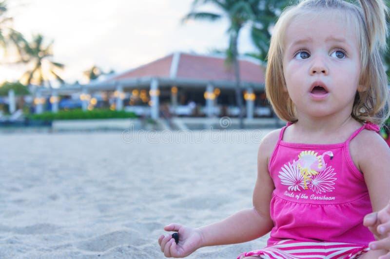 Bébé jouant sur la plage Elle a ouvert sa bouche dans la surprise photo stock