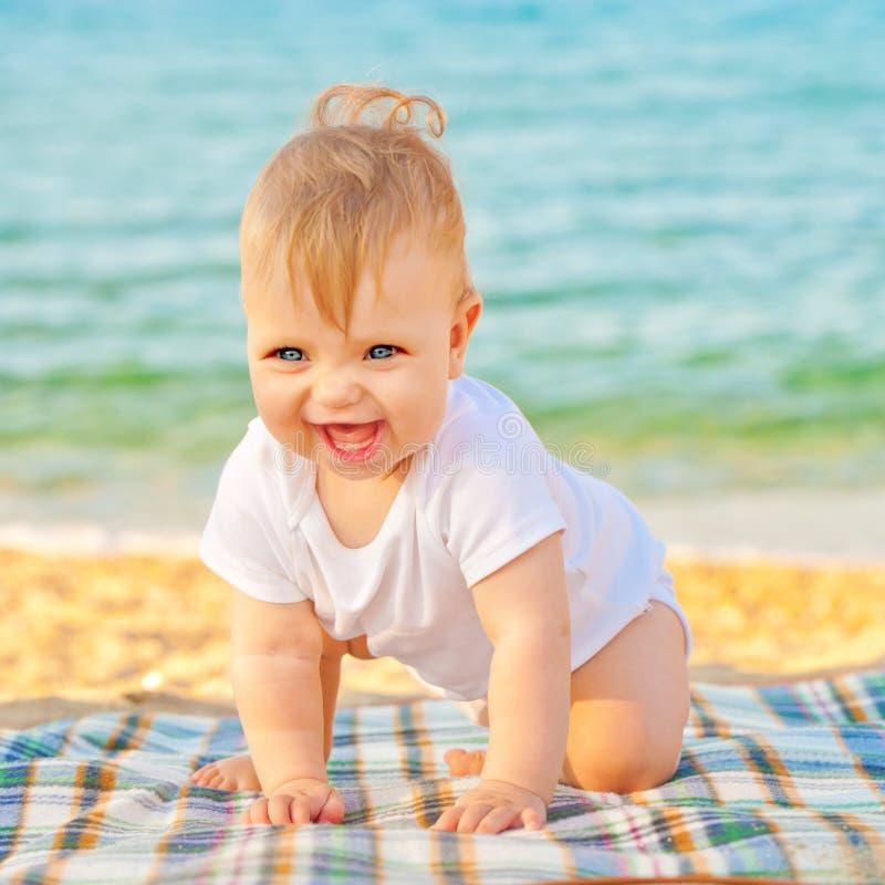 Bébé jouant sur la plage près de la mer image libre de droits
