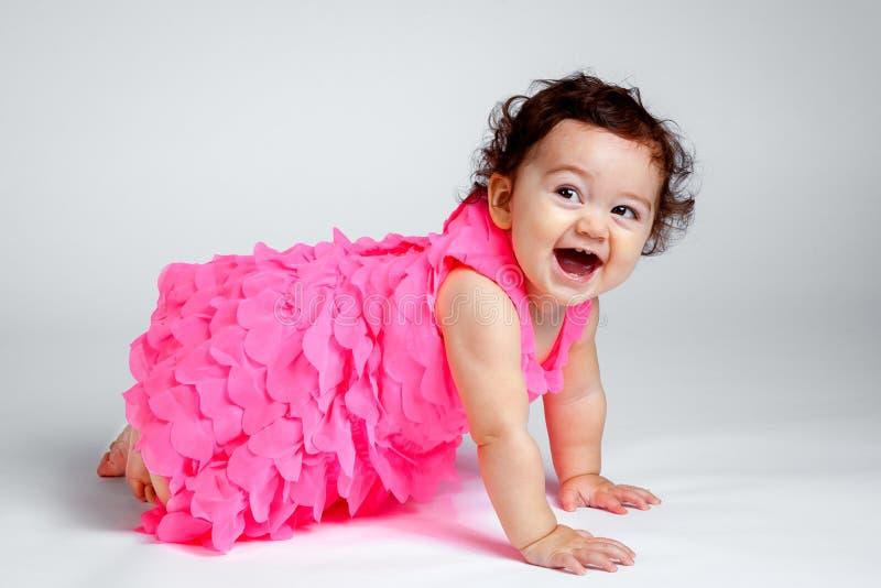 Bébé joyeux avec les cheveux bouclés rampant et riant photos stock
