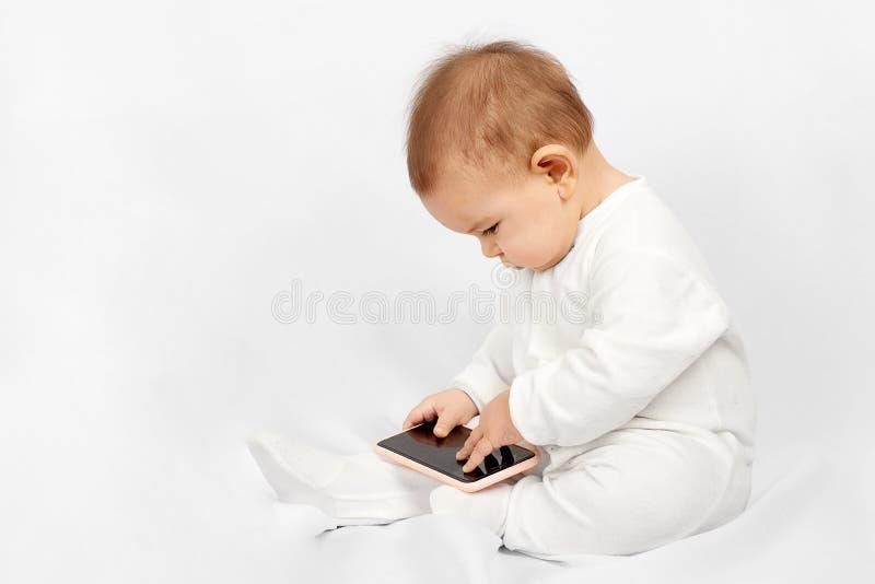Bébé jugeant un téléphone portable d'isolement sur le fond blanc photographie stock libre de droits