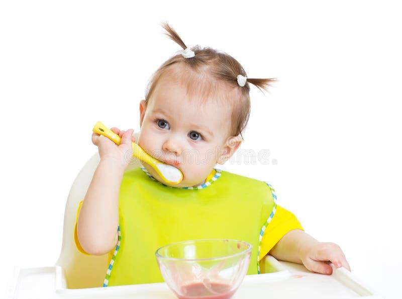 Bébé mangeant avec l'appétit se reposant à la table images stock