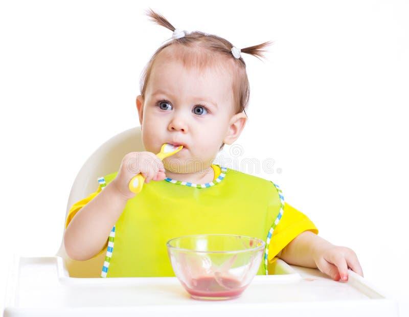 Bébé mangeant avec la cuillère se reposant à la table images libres de droits