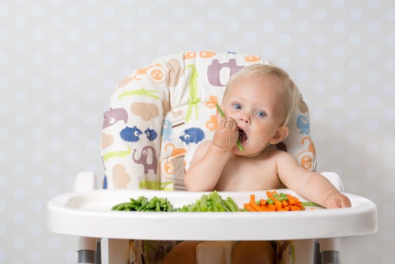 Bébé mangeant de la nourriture crue photographie stock libre de droits
