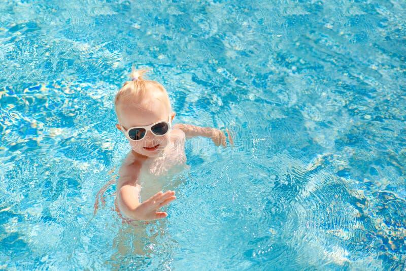 Bébé mignon éclaboussant dans la piscine pendant l'été images libres de droits