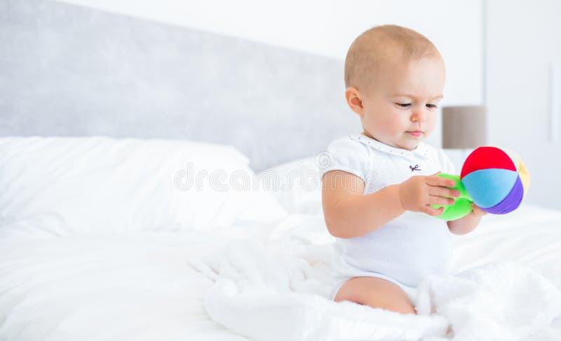 Bébé mignon avec le jouet se reposant sur le lit image libre de droits