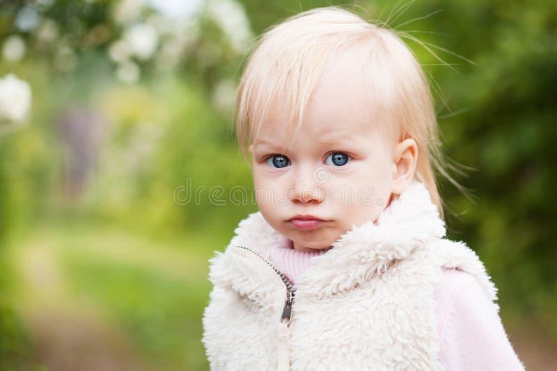 Bébé mignon avec les cheveux blonds dans le jardin de floraison images libres de droits