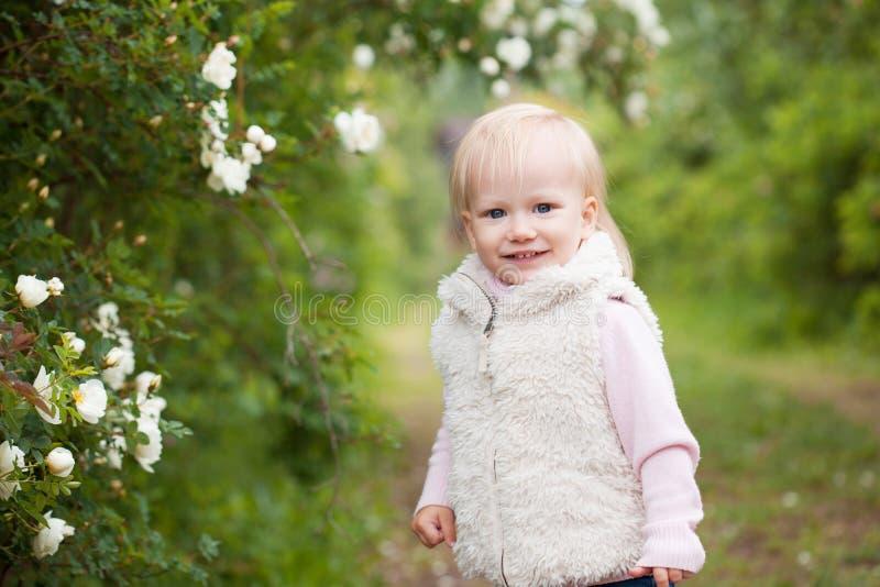 Bébé mignon avec les cheveux blonds dans le jardin de floraison photographie stock libre de droits