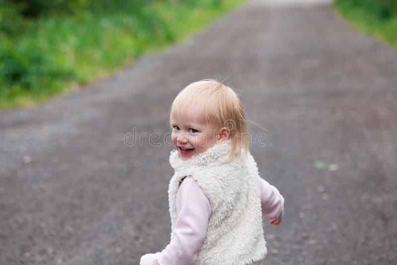 Bébé mignon avec les cheveux bouclés blonds dehors photo stock