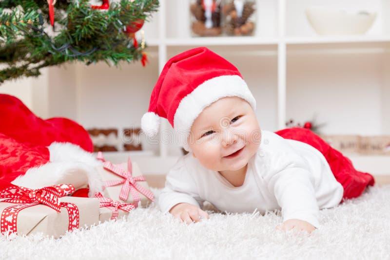 Bébé mignon dans un chapeau de Santa à côté d'arbre de Noël avec des présents photographie stock