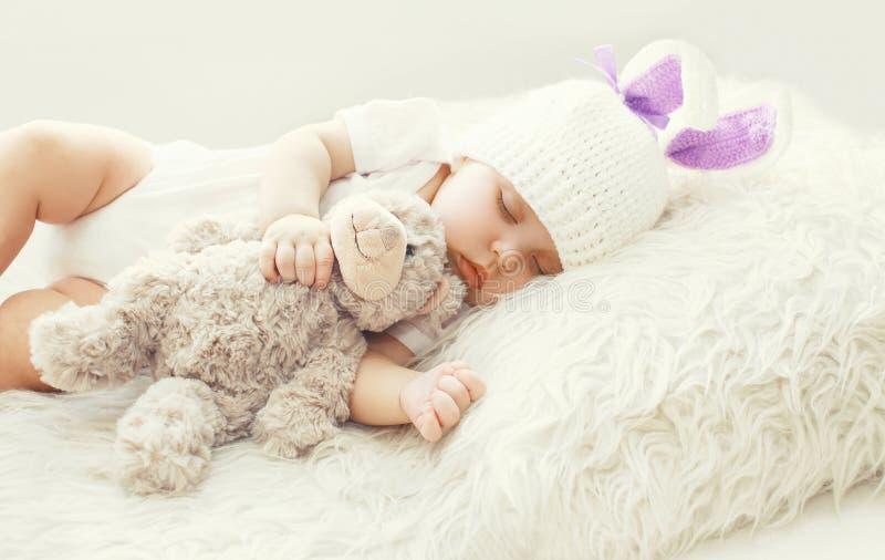 Bébé mignon dormant avec le jouet d'ours de nounours sur la maison molle blanche de lit photos libres de droits