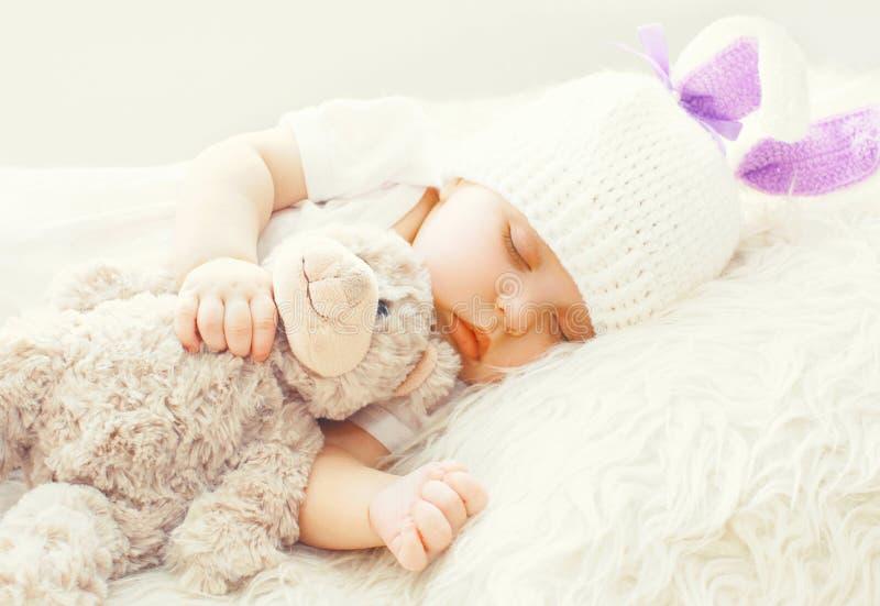 Bébé mignon dormant avec le jouet d'ours de nounours sur le lit mou blanc photographie stock libre de droits