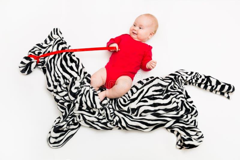Bébé mignon drôle s'asseyant sur le cheval de jouet ou le zèbre et le sourire photographie stock libre de droits