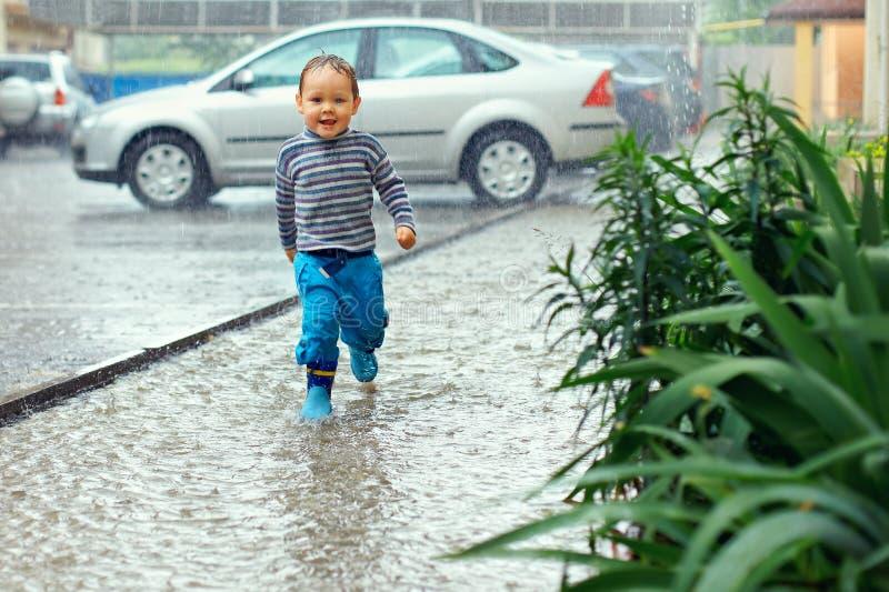 Bébé mignon exécutant sous la pluie photo stock
