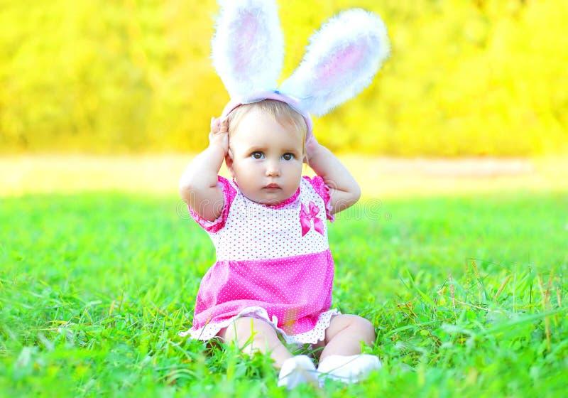 Bébé mignon heureux avec des oreilles de lapin sur l'herbe en ressort ensoleillé photographie stock