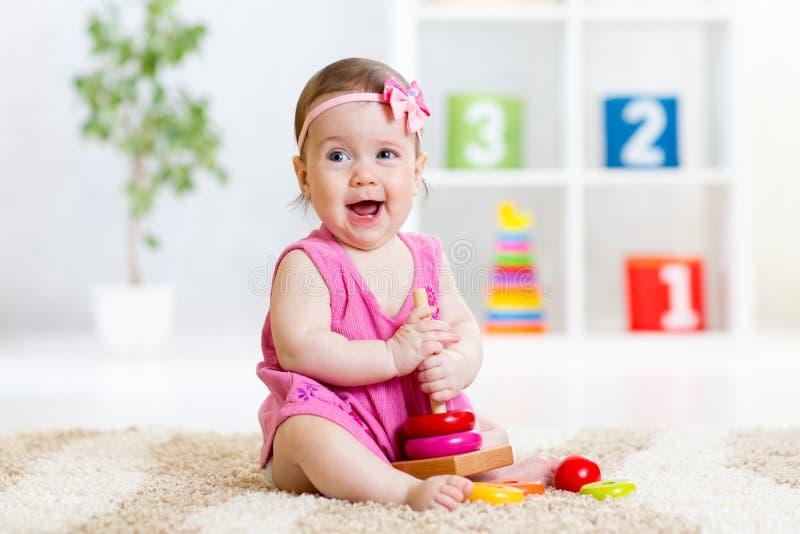 Bébé mignon jouant avec la pyramide colorée de jouet images libres de droits