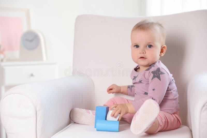 B?b? mignon jouant avec les blocs constitutifs dans le fauteuil ? la maison photo stock