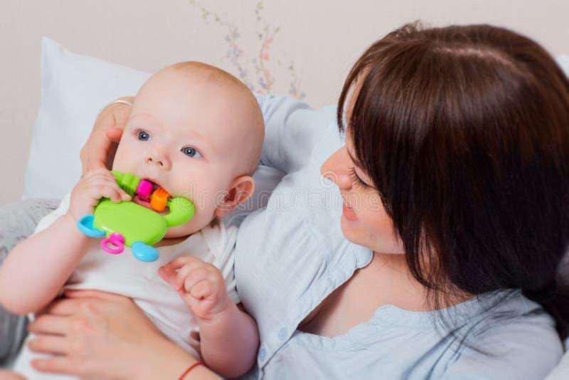 Bébé mignon jouant avec un jouet, mère souriant et étreignant l'enfant o image libre de droits