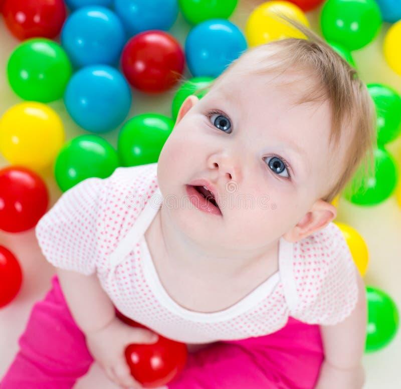 Bébé mignon jouant parmi les billes colorées photographie stock libre de droits