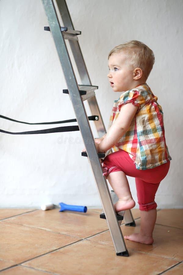 Bébé mignon s'élevant sur une échelle d'étape à l'intérieur photo stock